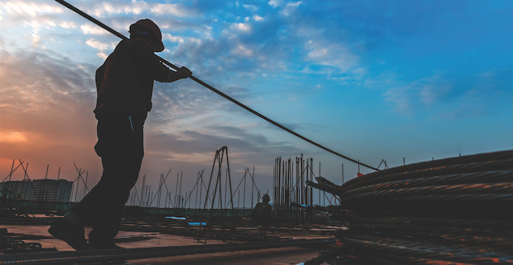 worker carries materials on construction site-labor shortage-lack of leadership