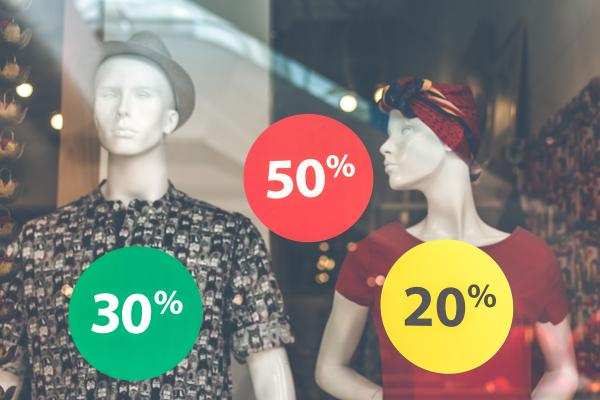 Mannequins with sale signs on store window