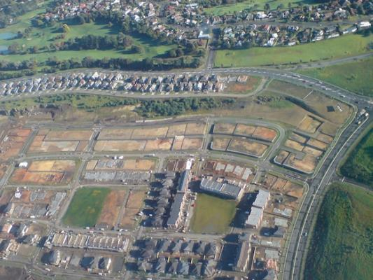 Aerial view of a housing subdivision with part complete and part still under construction.