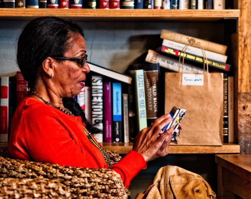 Woman using mobile device in a bookstore