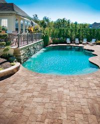 Panorama segmental pavers from Pavestone surround an organically shaped swimming pool.
