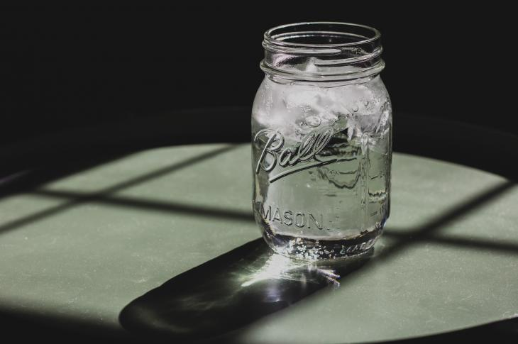 Mason jar with ice water in it on table