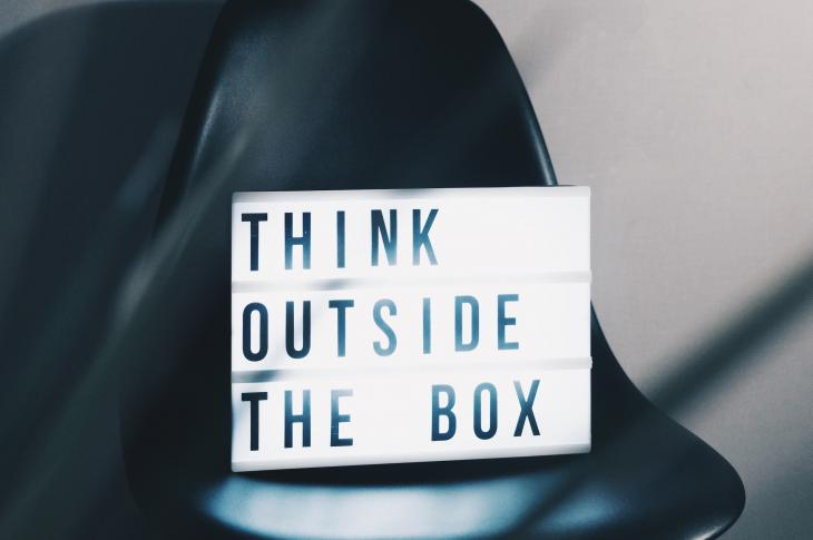Chair with illuminated sign on it saying 'think outside the box'
